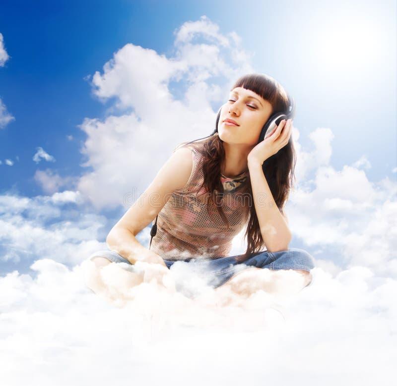 Música de escuta adolescente bonita nas nuvens imagens de stock