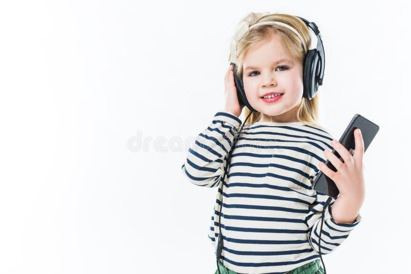 música de escuta adorável da criança pequena com fones de ouvido e smartphone imagens de stock
