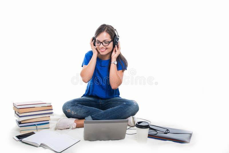 Música de escuta de assento da menina do estudante em fones de ouvido quando studdin fotografia de stock