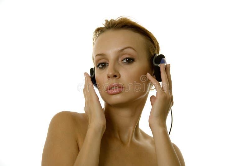 Música de escuta bonita da mulher nova imagens de stock
