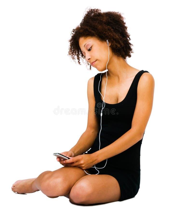 Música de escuta da jovem mulher imagem de stock