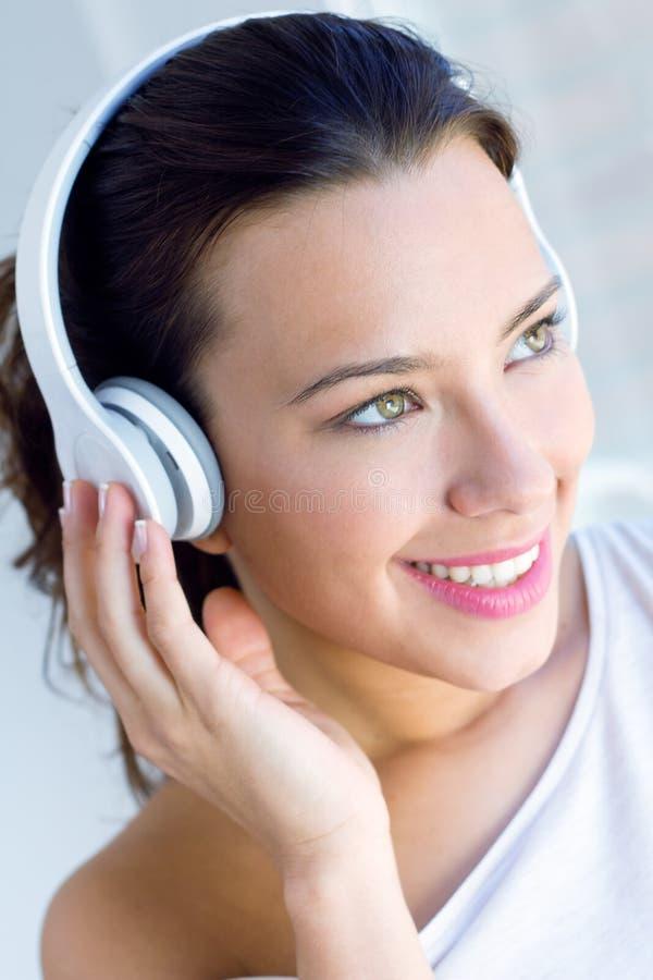 Música de escuta da jovem mulher bonita em casa