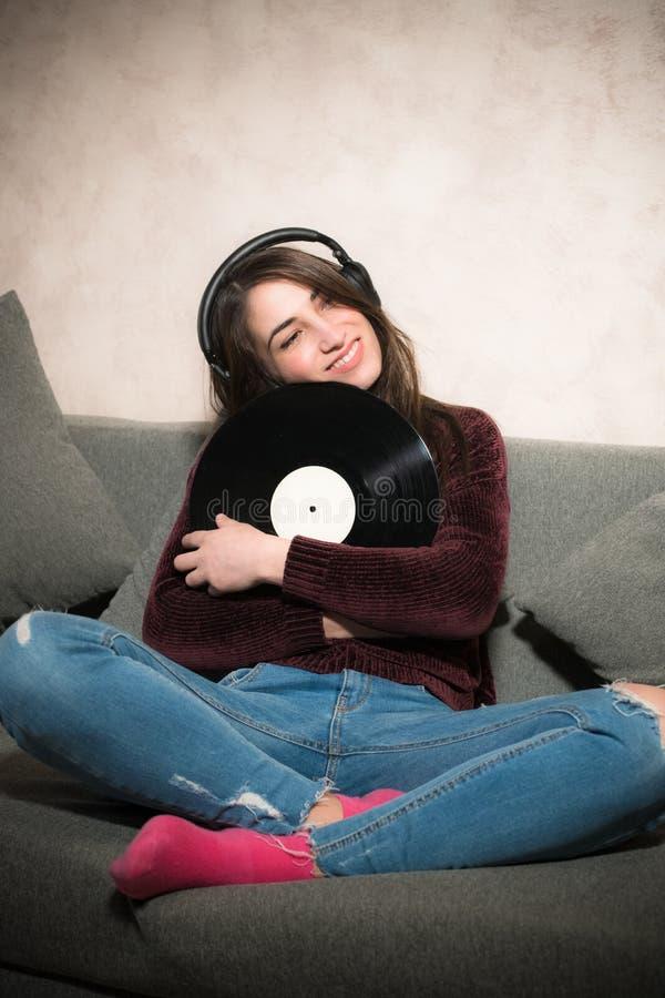Música de escuta da jovem mulher com registro de vinil fotos de stock