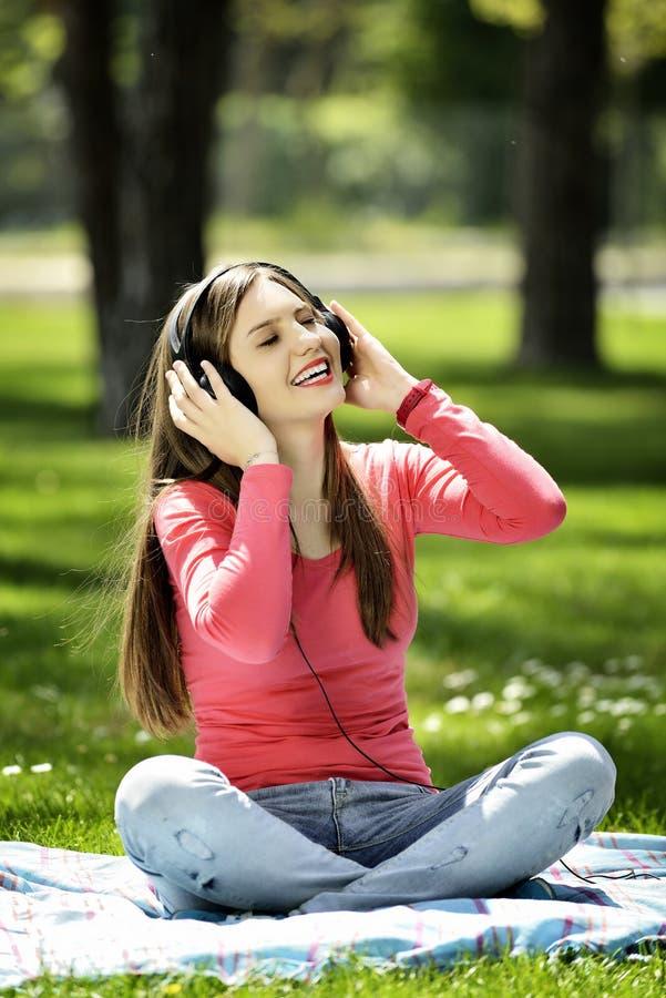 A música de escuta da jovem mulher na natureza é meu passatempo imagens de stock