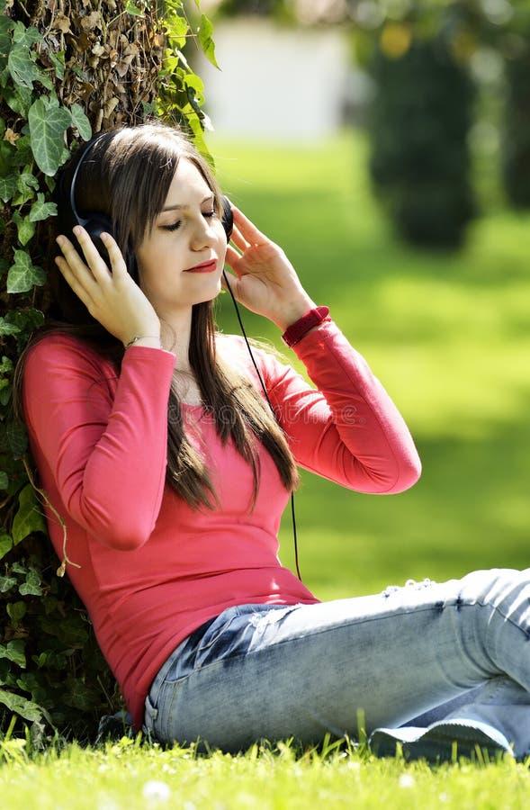 A música de escuta da jovem mulher na natureza é meu passatempo foto de stock