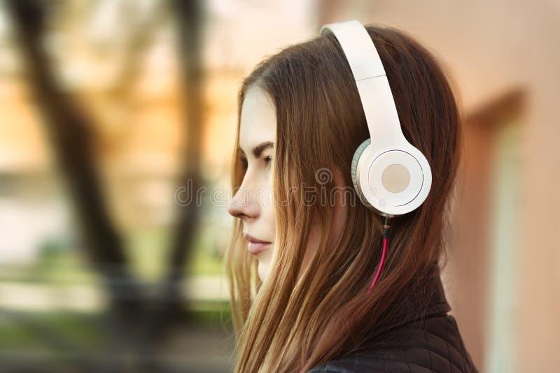 Música de escuta da jovem mulher nos fones de ouvido na cidade foto de stock
