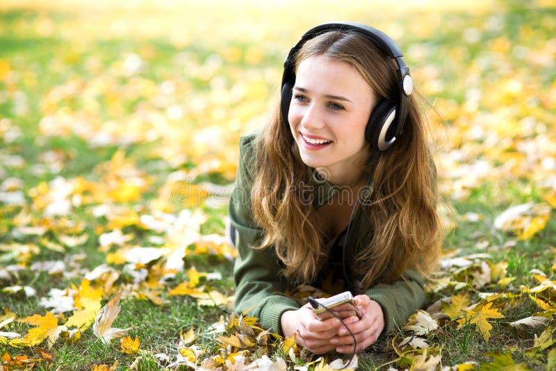 Música de escuta da menina ao ar livre foto de stock royalty free