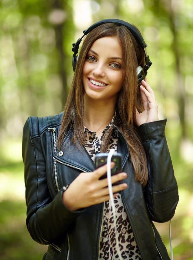 Música de escuta da menina ao ar livre foto de stock