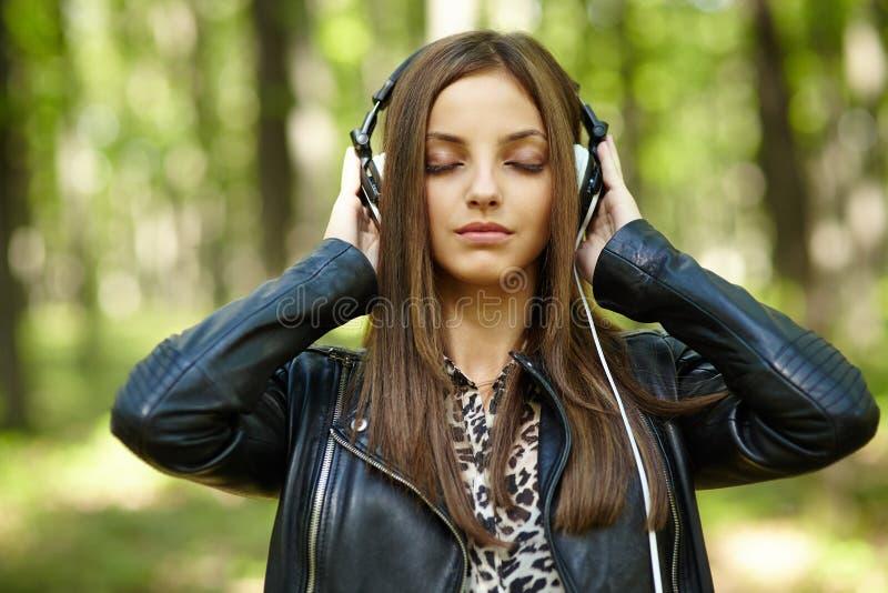 Música de escuta da menina ao ar livre imagem de stock