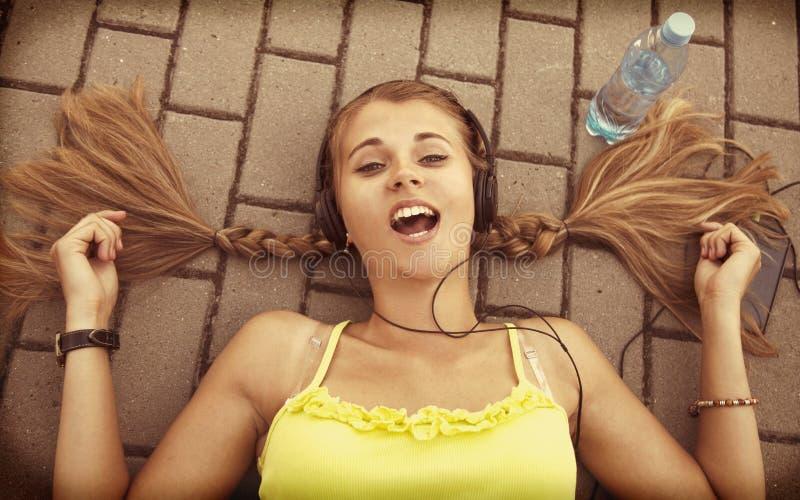 Música de escuta da menina atrativa nova feliz com fones de ouvido fotos de stock royalty free