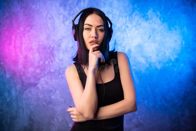 Música de escuta da menina bonita em fones de ouvido grandes imagem de stock royalty free