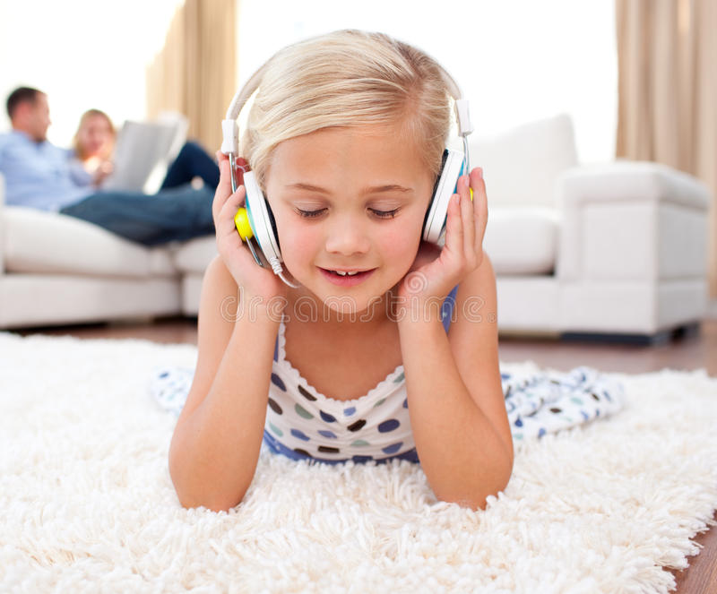 Música de escuta da menina bonito que encontra-se no assoalho fotos de stock royalty free