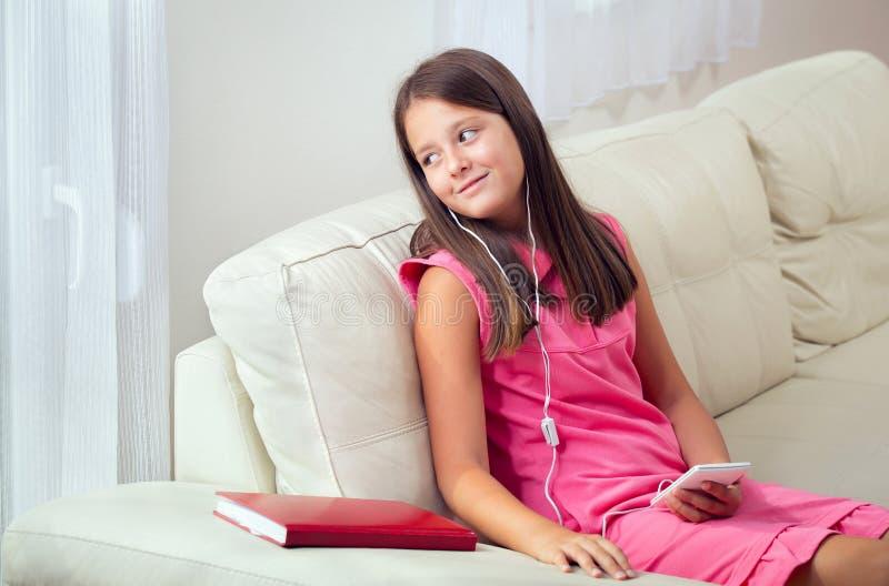 Música de escuta da menina do smartphone com os fones de ouvido na sala de visitas em casa foto de stock royalty free