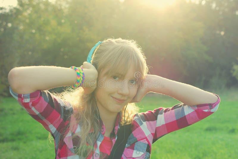 Música de escuta da menina no prado no estilo do vintage imagens de stock