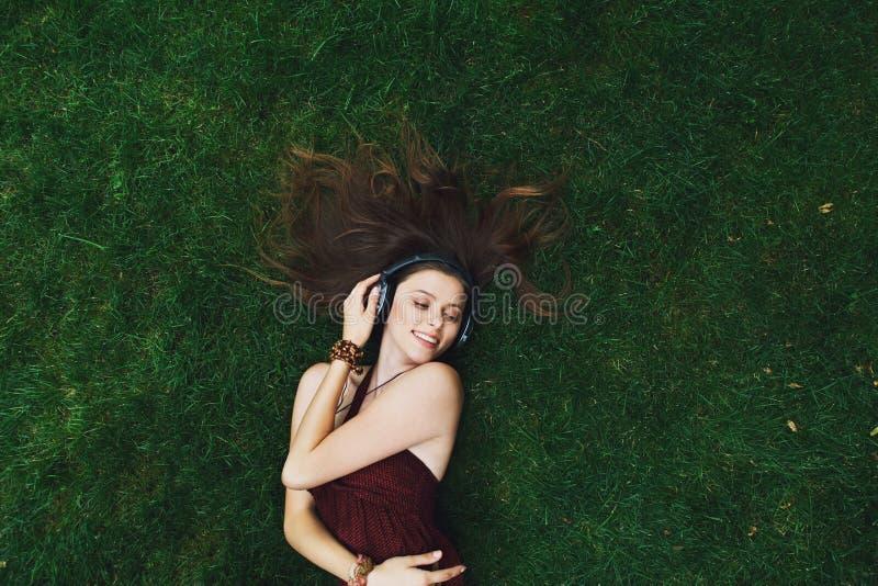 Música de escuta da moça bonita nos fones de ouvido que encontram-se na grama imagem de stock