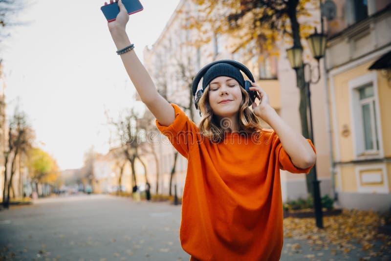 Música de escuta da moça bonito nos fones de ouvido, dansing e guardando o telefone celular à disposição, estilo urbano, moderno  fotos de stock