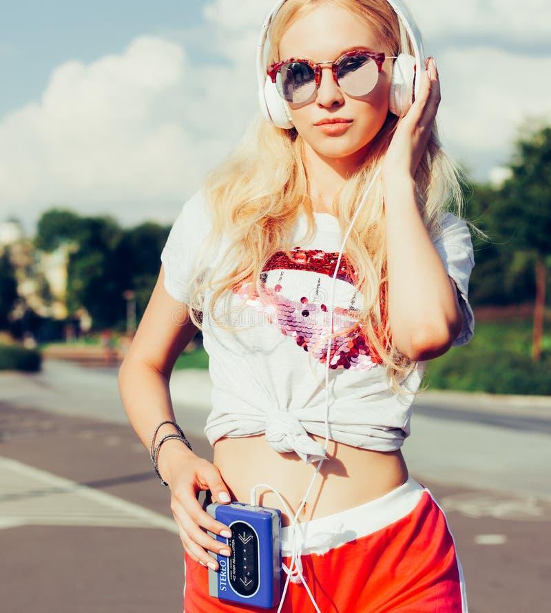 Música de escuta da moça nos fones de ouvido, no estilo urbano da rua, na mulher exterior do moderno do estilo da rua nos óculos  foto de stock