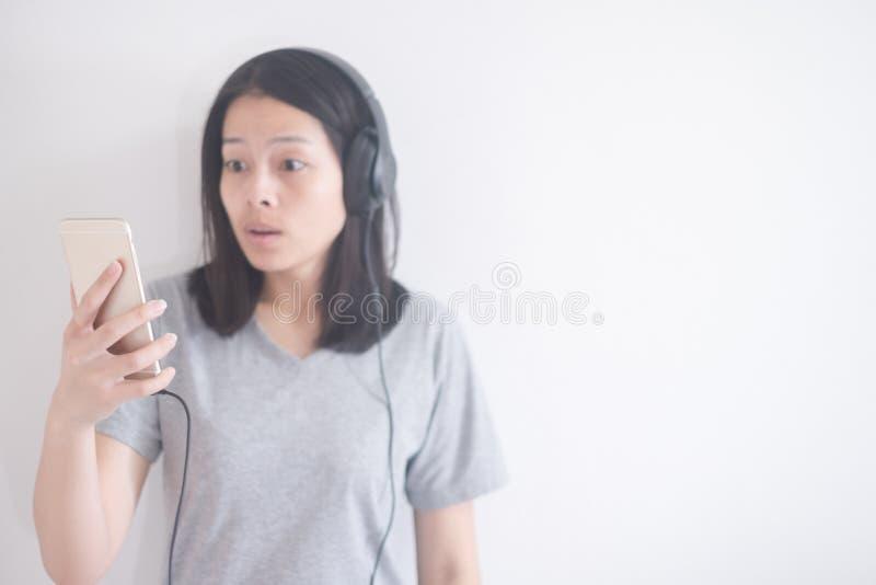 Música de escuta da mulher asiática bonita com fones de ouvido e smartphone em um foco seletivo do fundo branco imagem de stock royalty free