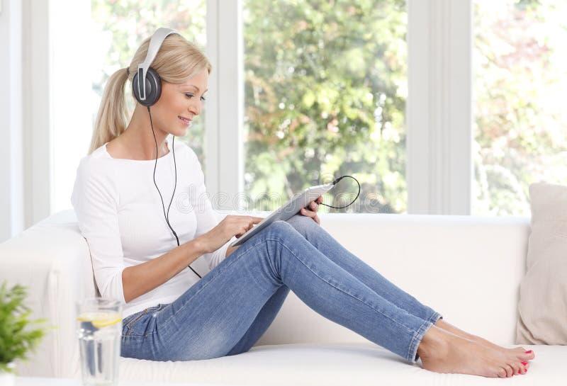 Música de escuta da mulher bonita em casa foto de stock