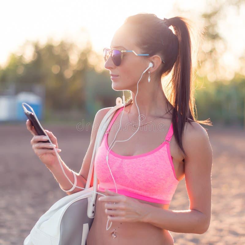 Música de escuta da mulher do atleta que olha o smartphone após o exercício na noite do verão do retrato da natureza fora no foto de stock royalty free