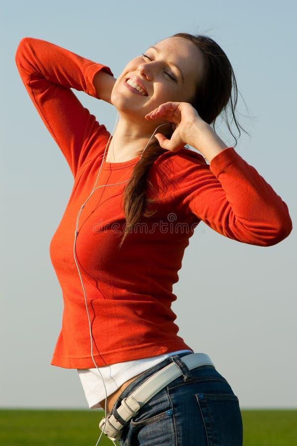 Música de escuta da mulher do smiley fotos de stock royalty free