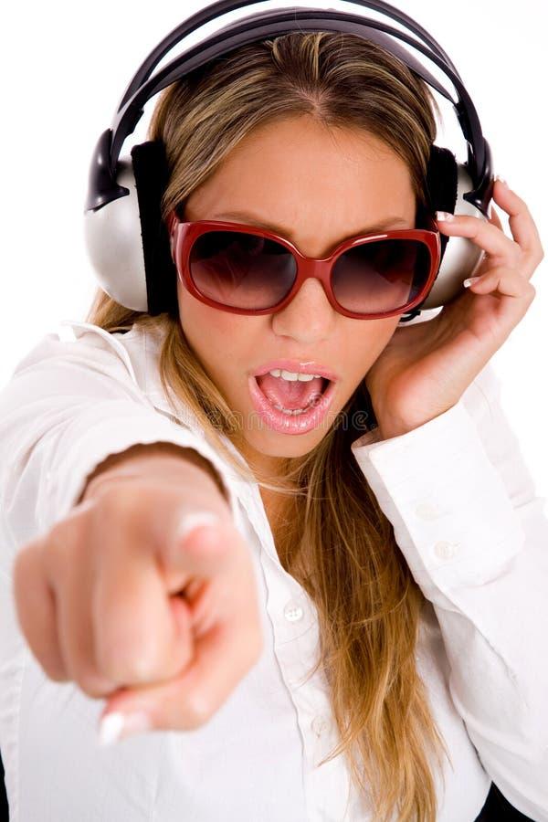 Música de escuta da mulher e apontar na câmera imagem de stock