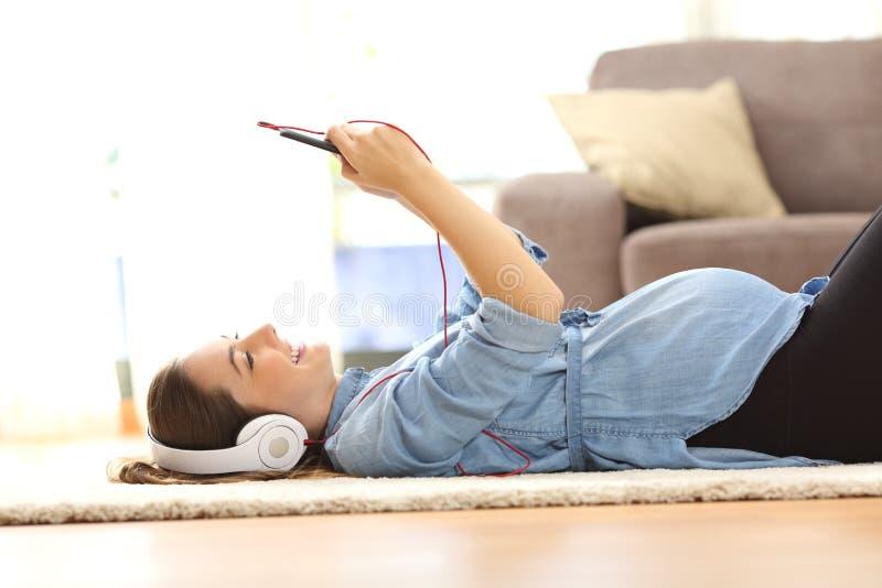Música de escuta da mulher gravida com fones de ouvido imagens de stock