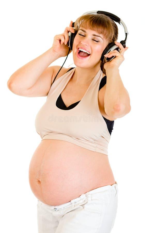 Música de escuta da mulher gravida feliz nos auscultadores fotos de stock royalty free