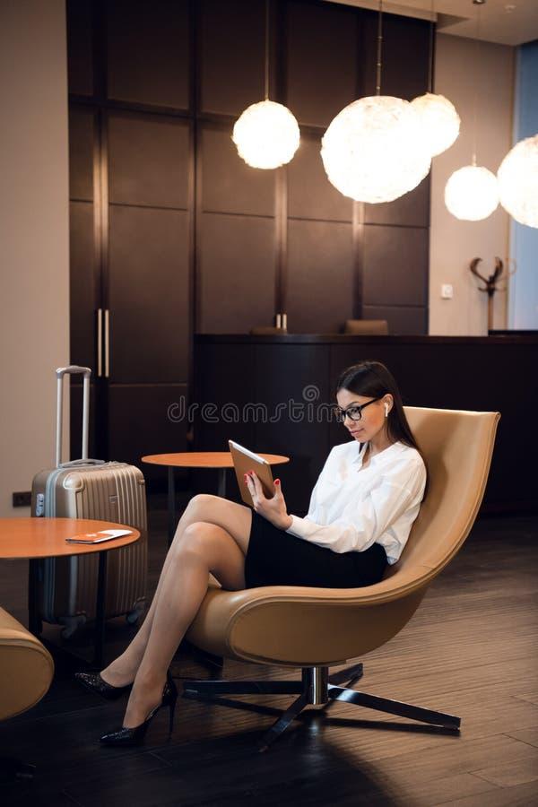 Música de escuta da mulher de negócios segura em seu tablet pc ao sentar-se na cadeira na sala de estar do negócio do aeroporto fotografia de stock royalty free