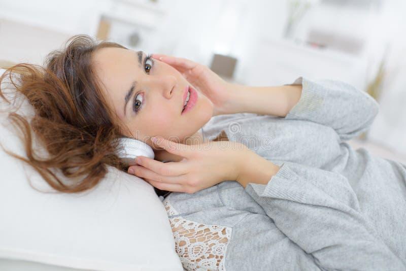Música de escuta da mulher nos fones de ouvido em casa foto de stock royalty free