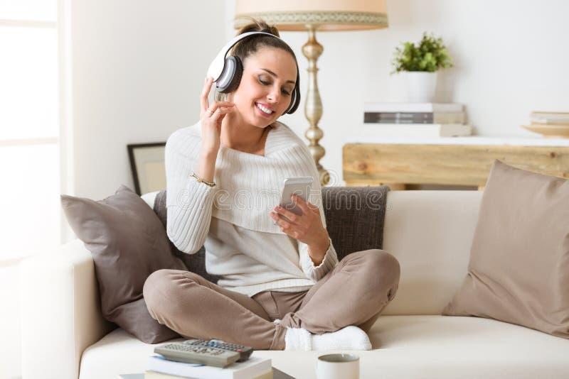Música de escuta da mulher nos fones de ouvido em um sofá imagem de stock royalty free