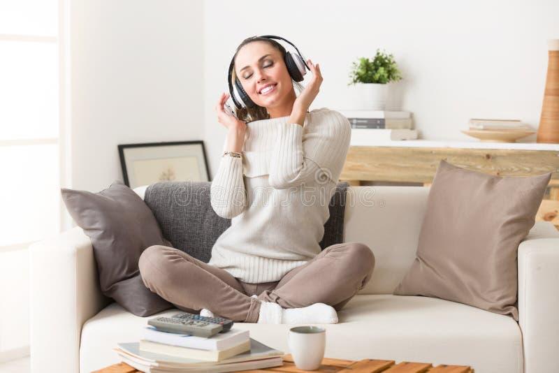 Música de escuta da mulher nos fones de ouvido em um sofá imagens de stock royalty free