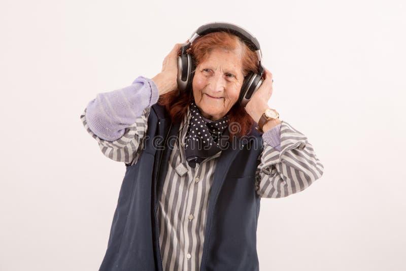 Música de escuta da senhora idosa com fones de ouvido fotografia de stock
