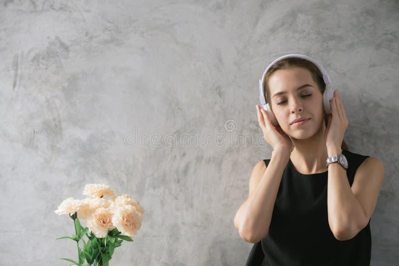 Música de escuta das jovens mulheres ao pensar, mulher que faz trabalhos de casa no lugar moderno, mulher que trabalha com concei fotografia de stock