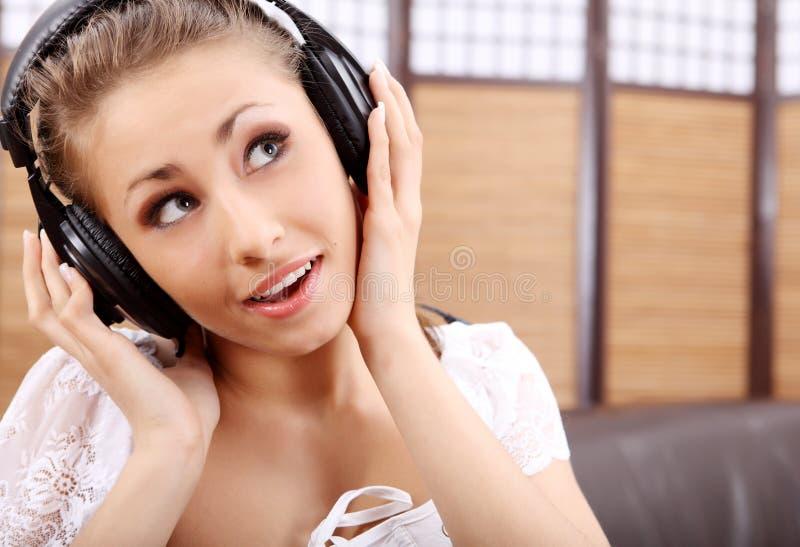 Música de escuta das mulheres 'sexy' fotografia de stock royalty free