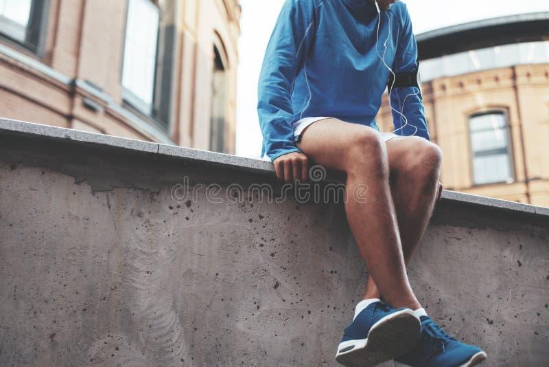 Música de escuta do atleta em tênis de corrida azuis, sentando-se e descansando após a sessão do exercício da rua imagem de stock