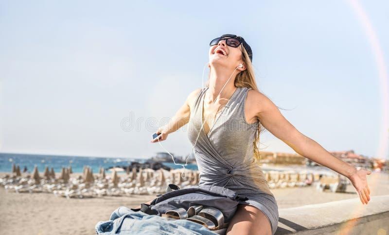Música de escuta do blogger do curso da jovem mulher na praia do Los Cristianos foto de stock