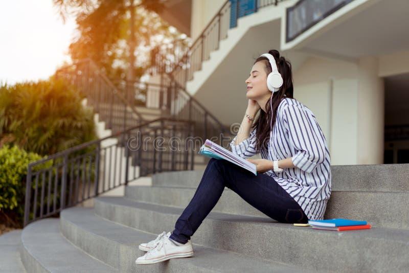 Música de escuta do estudante dos adolescentes da jovem mulher fotos de stock royalty free