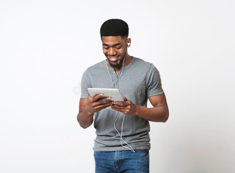 Música de escuta do homem afro-americano com fones de ouvido e a tabuleta digital fotografia de stock royalty free