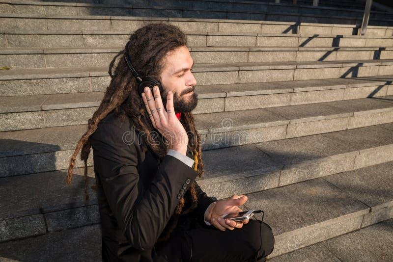 Música de escuta do homem de negócios elegante à moda dos dreadlocks fotos de stock royalty free