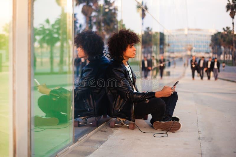Música de escuta do homem negro novo com móbil e fones de ouvido na cidade ensolarada fotos de stock