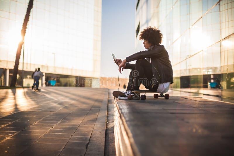 Música de escuta do homem negro novo com móbil e fones de ouvido na cidade ensolarada foto de stock royalty free