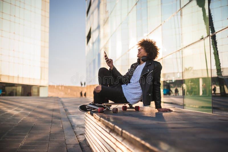 Música de escuta do homem negro novo com móbil e fones de ouvido na cidade ensolarada fotos de stock royalty free