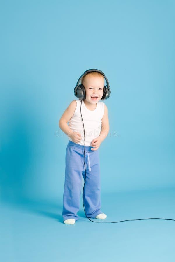 Música de escuta do menino alegre em auscultadores do cabo imagens de stock