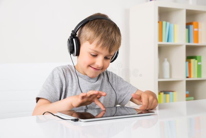 Música de escuta do menino na tabuleta de Digitas imagem de stock royalty free