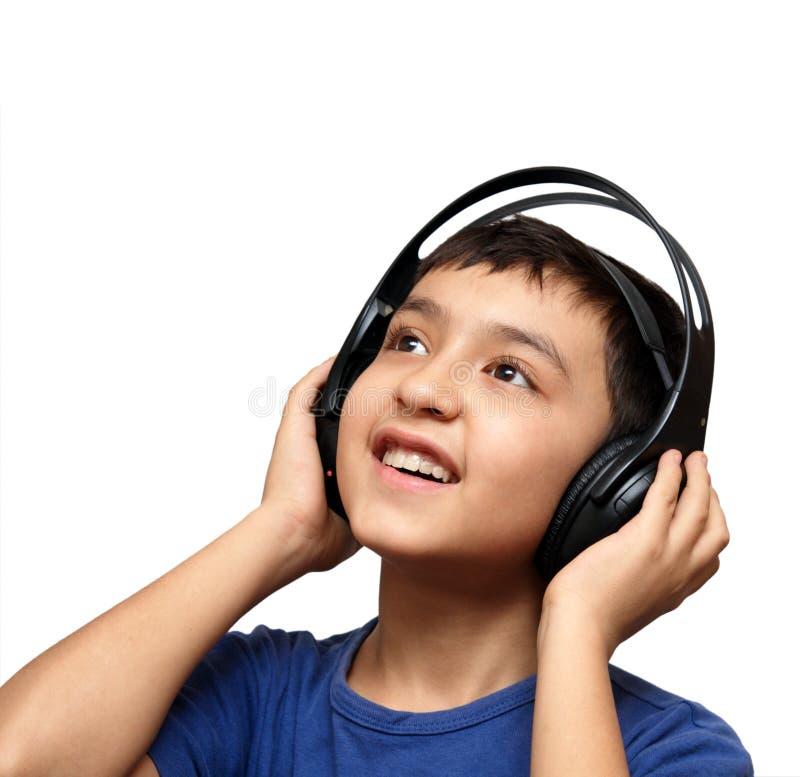 Música de escuta do menino nos auscultadores fotografia de stock royalty free