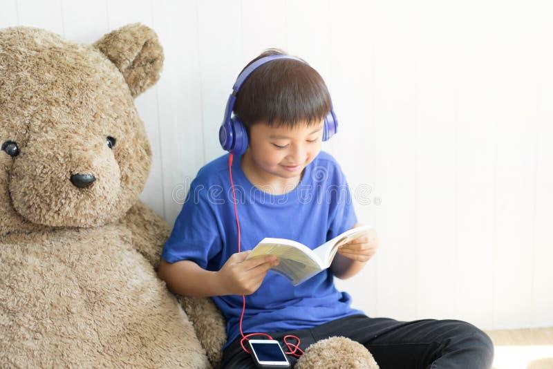 Música de escuta do rapaz pequeno e para ler um livro para para relaxar foto de stock royalty free