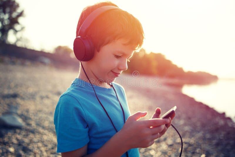 Música de escuta do rapaz pequeno na tabuleta no por do sol exterior fotografia de stock