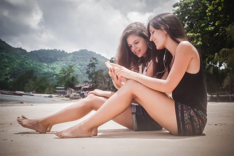 Música de escuta de dois melhores amigos no smartphone, apreciando na praia imagens de stock royalty free