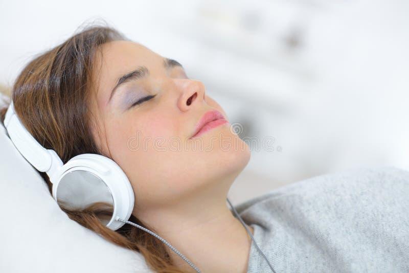 Música de escuta dos fones de ouvido bonitos novos da mulher na opinião superior da cama fotos de stock